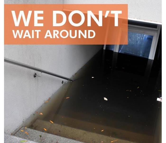 Flooded basement with the words on the left side of picture WE DON'T WAIT AROUND